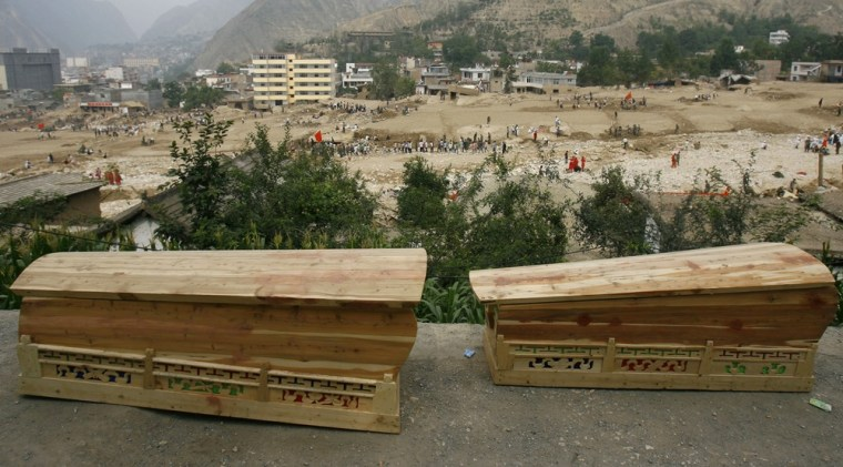 Image: Coffins lie near a site of the landslide-hit Zhouqu County of Gannan Tibetan Autonomous Prefecture