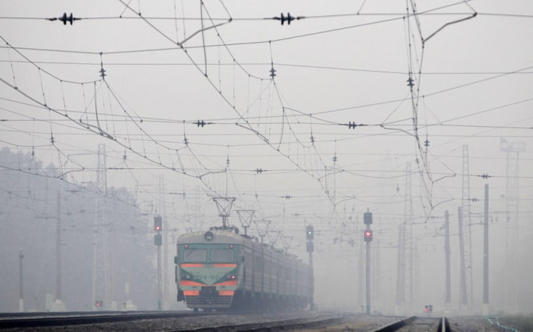 Image: A train travels in heavy smog at the railway station near the village of Kustarevka, southeast of Moscow