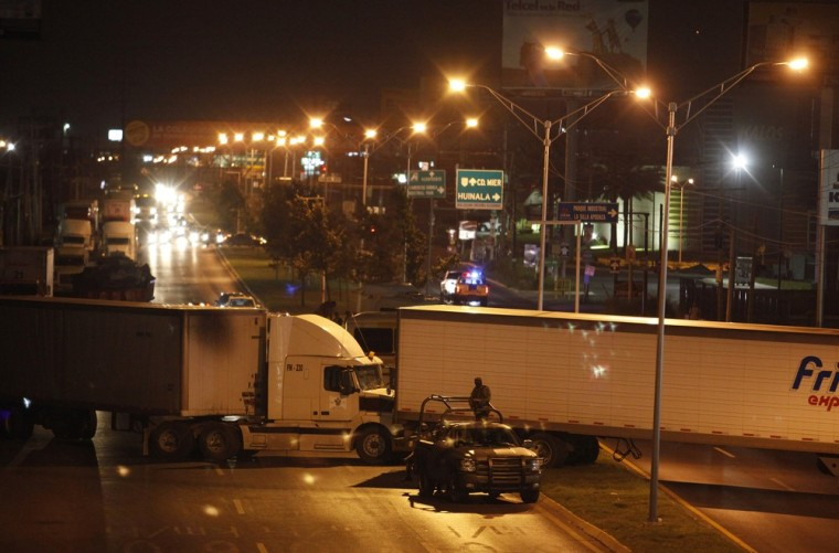 Image: Soldiers stand guard around stolen trailers used by gunmen to form a barricade to block a main road in Monterrey