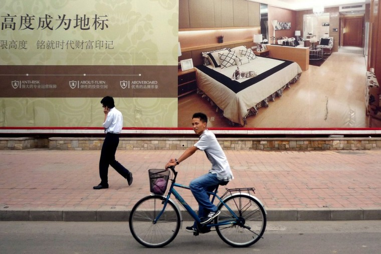 Image: A man and a cyclist pass a billboard advertising luxury apartments