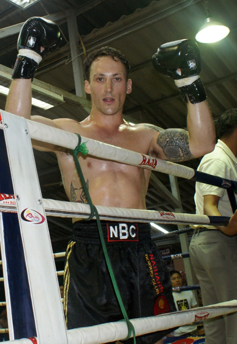 "Lee Aldhouse celebrates after winning a Muay Thai fight in Phuket in 2009. The letters on his waistband stand for ""Nai Harn Boxing Club."""