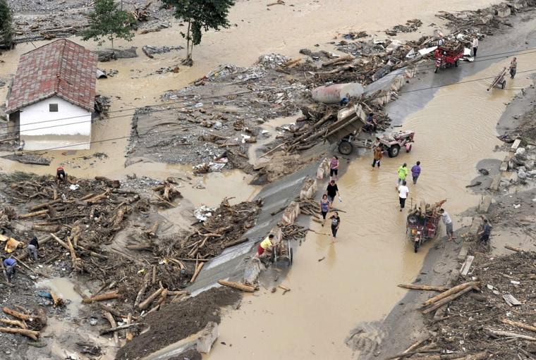 Image: People walk past debris after a mudslide hit Mianzhu, China