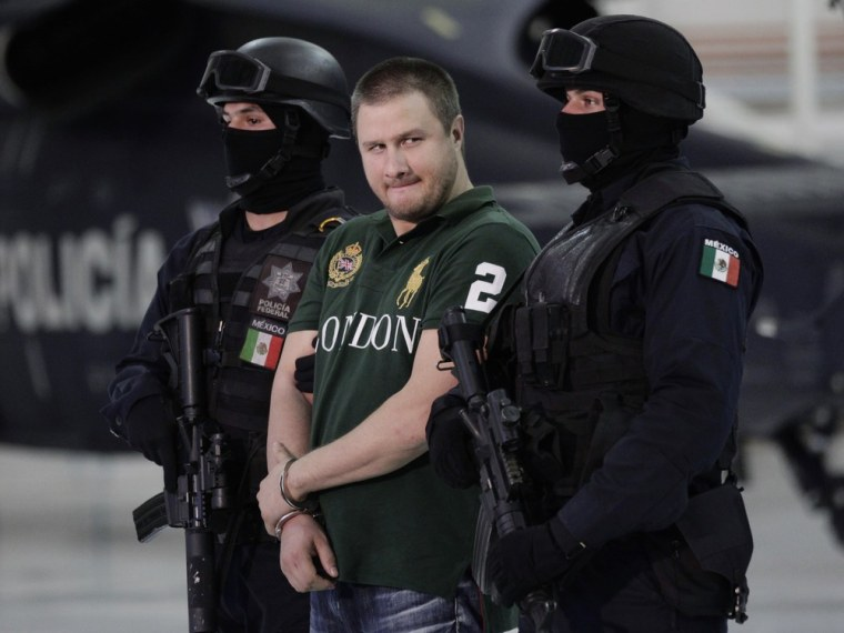 "Image: Major drug trafficker Edgar ""La Barbie"" Valdez is escorted by Mexican federal police during a news conference at the federal police center in Mexico City"