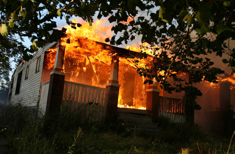 Flames engulfa homeon Detroit's east side Tuesday. Fire officials say flames swept through dozens of homes in Detroit, fanned by strong winds that toppled power lines across the city.