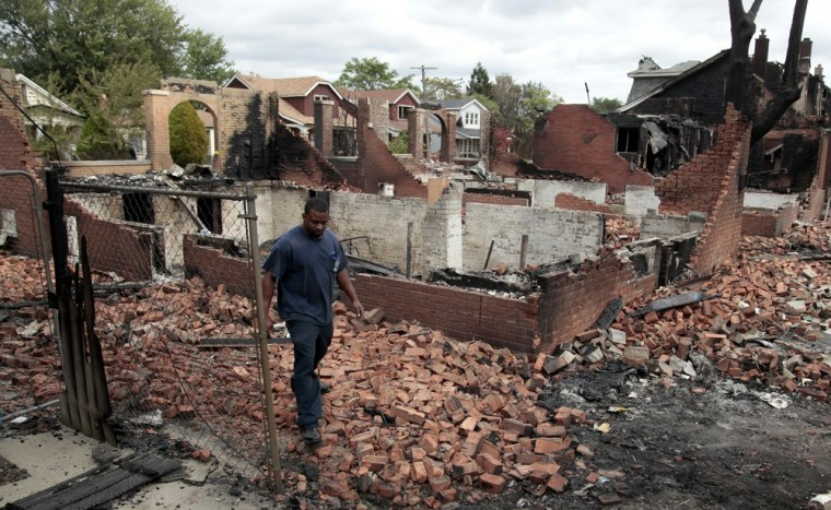 Image: A Detroit fire fighter looks through the smoldering back yards of burned homes and garages on East Robinwood in Detroit, Michigan