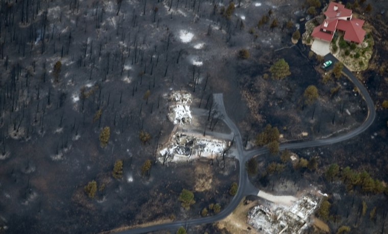 Image: An aerial view shows a seemingly untouched home next to two other homes that were destroyed by the Fourmile Canyon fire in Boulder, Colorado
