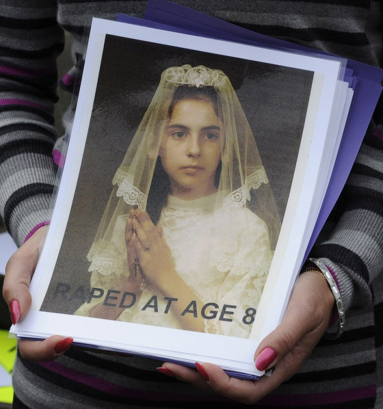 Image: Therese Albrecht and Barbara Blaine hold a picture of themselves during a protest by people assaulted by priests at St Mary's cathedral in Edinburgh