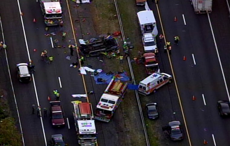 Rescuers respond Saturday to a accident that killed at least six people when a church minivan collided with a tractor-trailer on the New York StattThruway in Woodbury, N.Y.