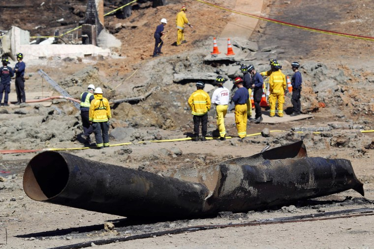 A wrecked gas pipe lies on street as investigators gather at the scene of a natural gas explosion in San Bruno