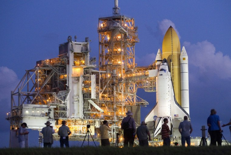 Image: Photographers gather to cover space shuttle Discovery as it sits on launch pad 39A after making the trip from the vehicle assembly building at the Kennedy Space Center in Cape Canaveral, Florida