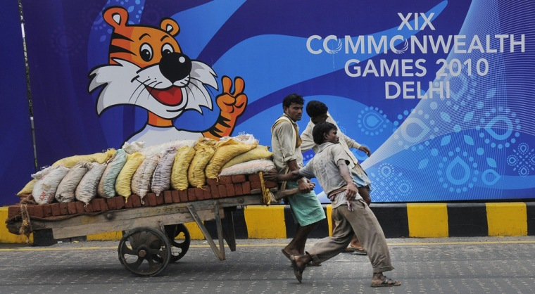 Image: Labourers pull a hand cart loaded with bricks and sacks of sand in front of boards advertising the 2010 Commonwealth Games in New Delhi
