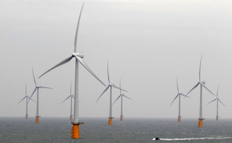 Image: A boat powers past the Thanet Offshore Wind Farm off the Kent coast in southern England