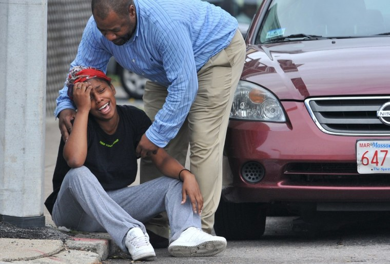 Image: A man comforts a grieving woman near the scene of a shooting i