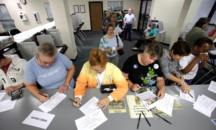 Image: Voters fill out paperwork for their absentee ballots on the first day of early voting for the November general election