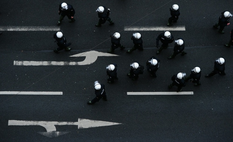 Image: TOPSHOTS Riot police officers walk past