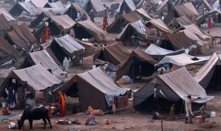 People stand outside their tents at a camp for those displaced by floods in Sukkur, southern Pakistan.