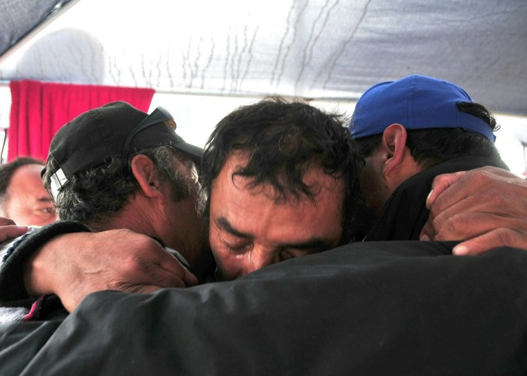 Image: Relatives of the trapped miners celebrat