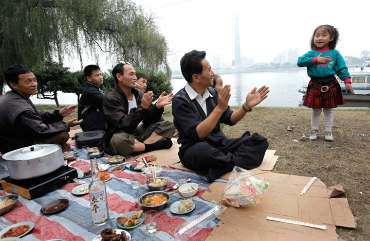 Image: A North Korean girl sings as her family have a picnic along the Taedong River in Pyongyang, North Korea