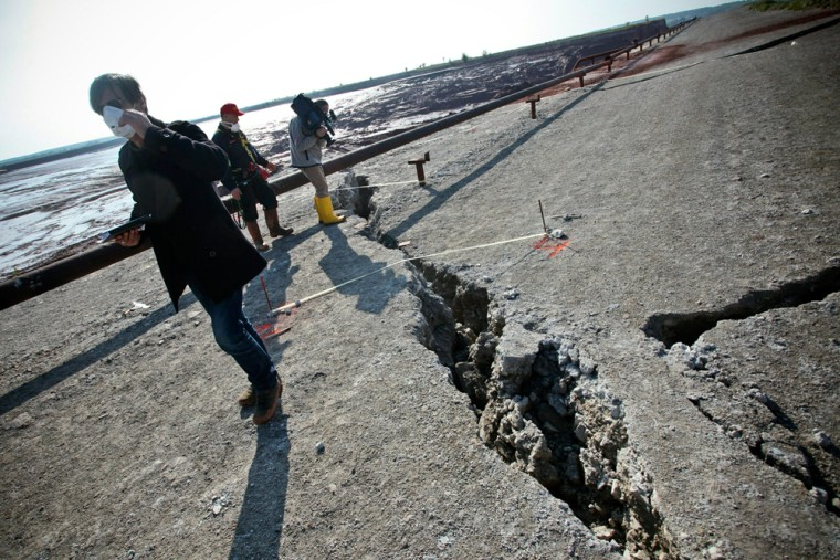 Image: A TV crew films a crack on the ruptured reservoir wall of the aluminum plant near Ajka.