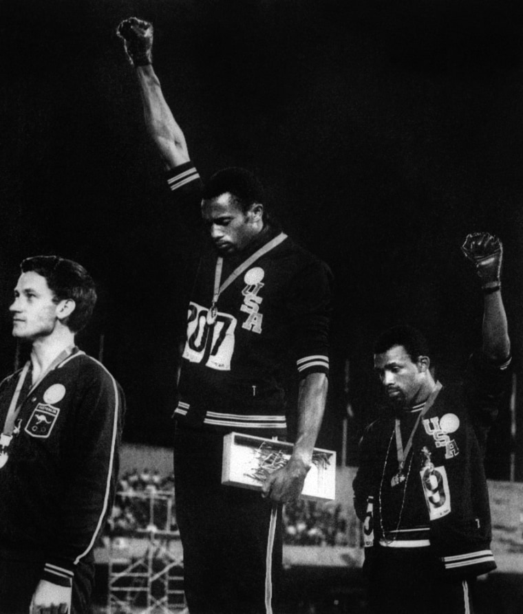 Image: US athletes Tommie Smith and John Carlos raise their gloved fists in the Black Power salute during the US national anthem