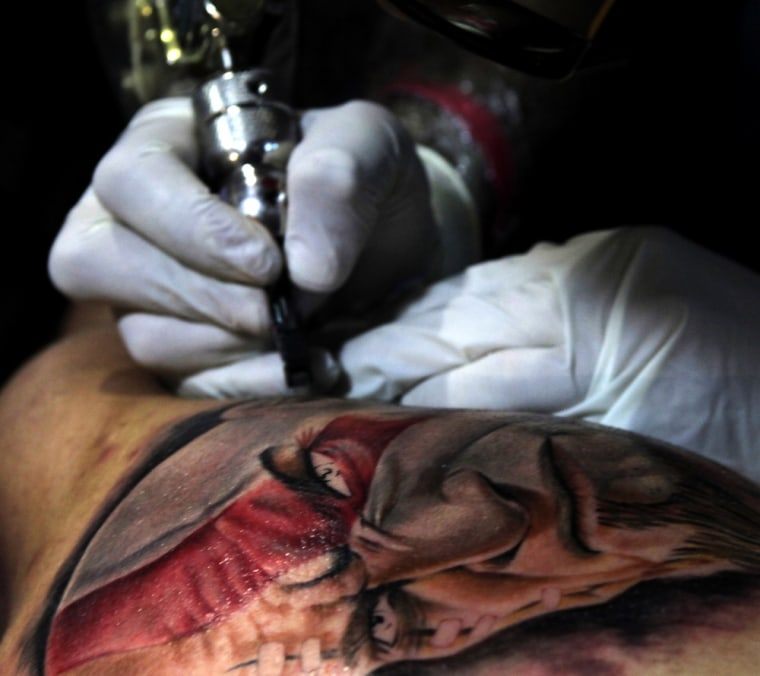 Image: A tattoo artist works on a man during the Bogotattoo Festival in Bogota