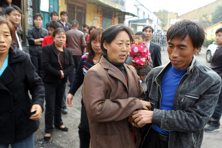 Image: Family members of the trapped miners console each other outside the mine in Yuzhou