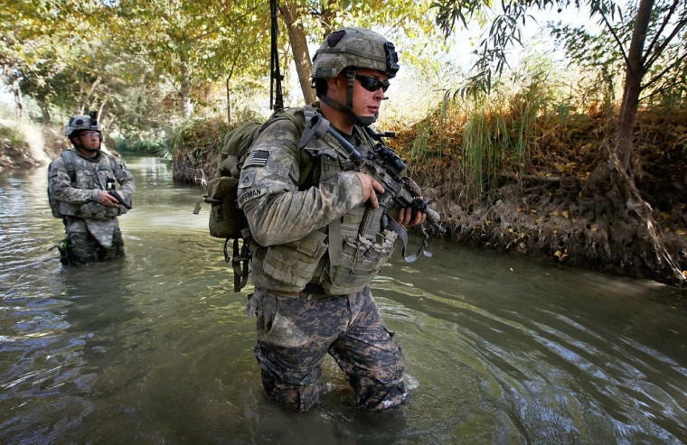 Image: Pfc. Michael Huffman of the the U.S. Army's 101st Airborne Division wades through a creek while on patrol to avoid buried bombs in Zhari district west of Kandahar,