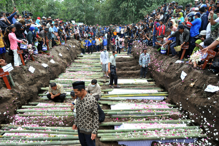 Image: Relatives sprinkle flower petals over the coffins of the victims of the Mount Merapi eruption during a mass funeral in Sidorejo