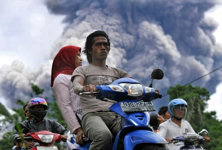 Image: Local residents leave a danger zone as MMerapi volcano releases ash clouds in Balerante village, Klaten