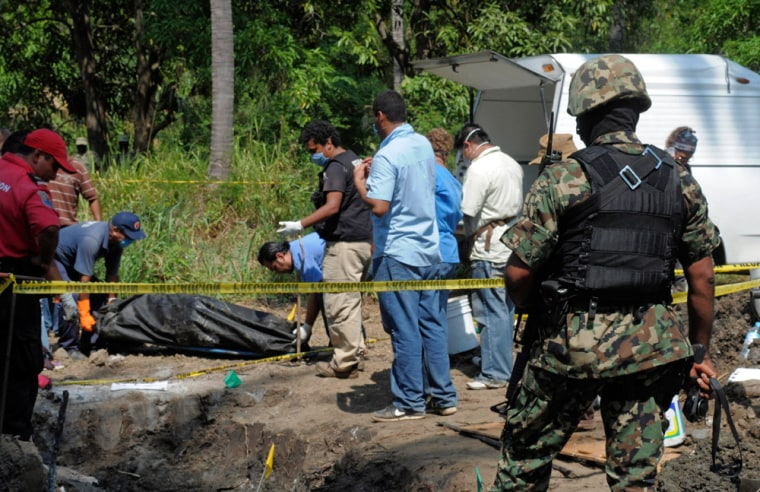 Image: A Mexican Navy soldier watches as forensic workers remove a body which was buried at a field in the town of Tuncingo