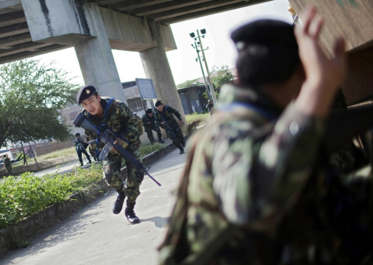 Image: Thai soldiers run for cover near the Thai-Myanmar border in Mae Sot,