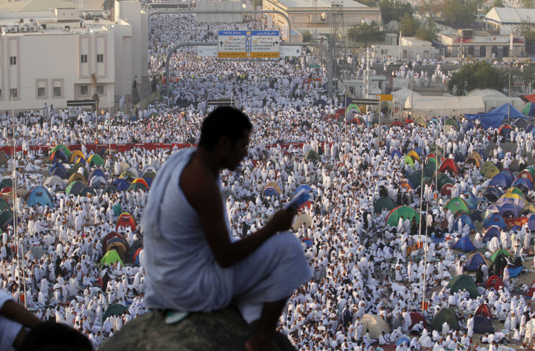 Image: A Muslim pilgrim prays on a rocky hill called the Mountain of Mercy