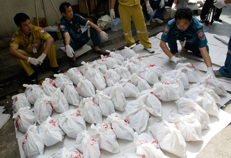 Image: Rescue workers arrange bags containing dead fetuses found at the morgue of a Buddhist temple in Bangkok,