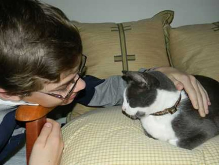 Scrub, a cat that went missing for five years in the aftermath of Hurricane Katrina, is petted by one of his owners, Matthew Noble. The feline was reunited after the Humane Society of South Mississippi identified him via a microchip.