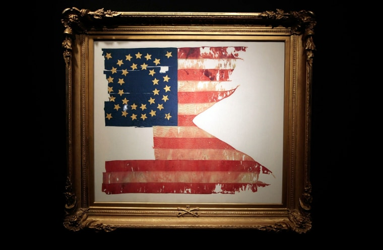 """Image: """"Custer's Last Flag"""" is seen in a frame at Sotheby's auction house"""