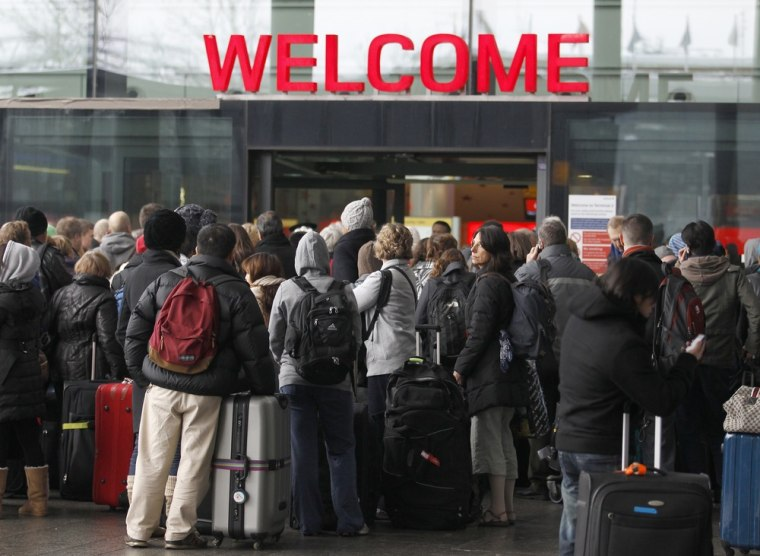 Image: Airline passengers queue to enter the departures area at Terminal 3 at Heathrow Airport in west London