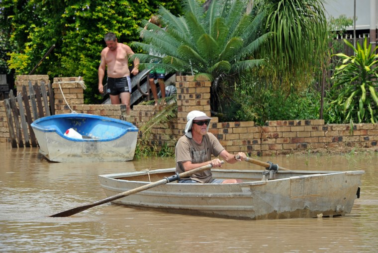 Image: Residents use boats to travel down the rroad after the swollen Fitzroy River broke its banks and flooded the city of Rockhampton