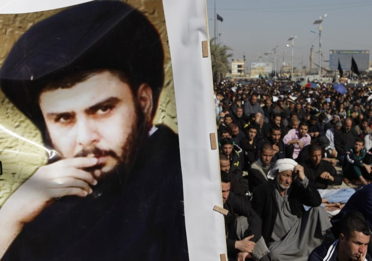 Image: Followers gather for prayers in Sadr City, Baghdad, beside a poster of Shiite cleric Muqtada al-Sadr