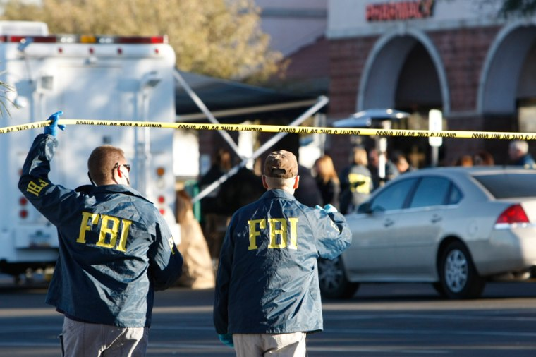 Image: FBI agents continue to process the shooting scene in Tucson