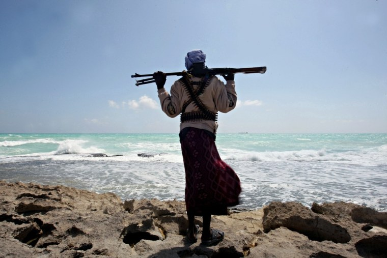 Image: An armed Somali pirate along the coastline