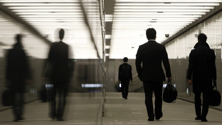 Image: Businessmen walk through a business complex in Tokyo