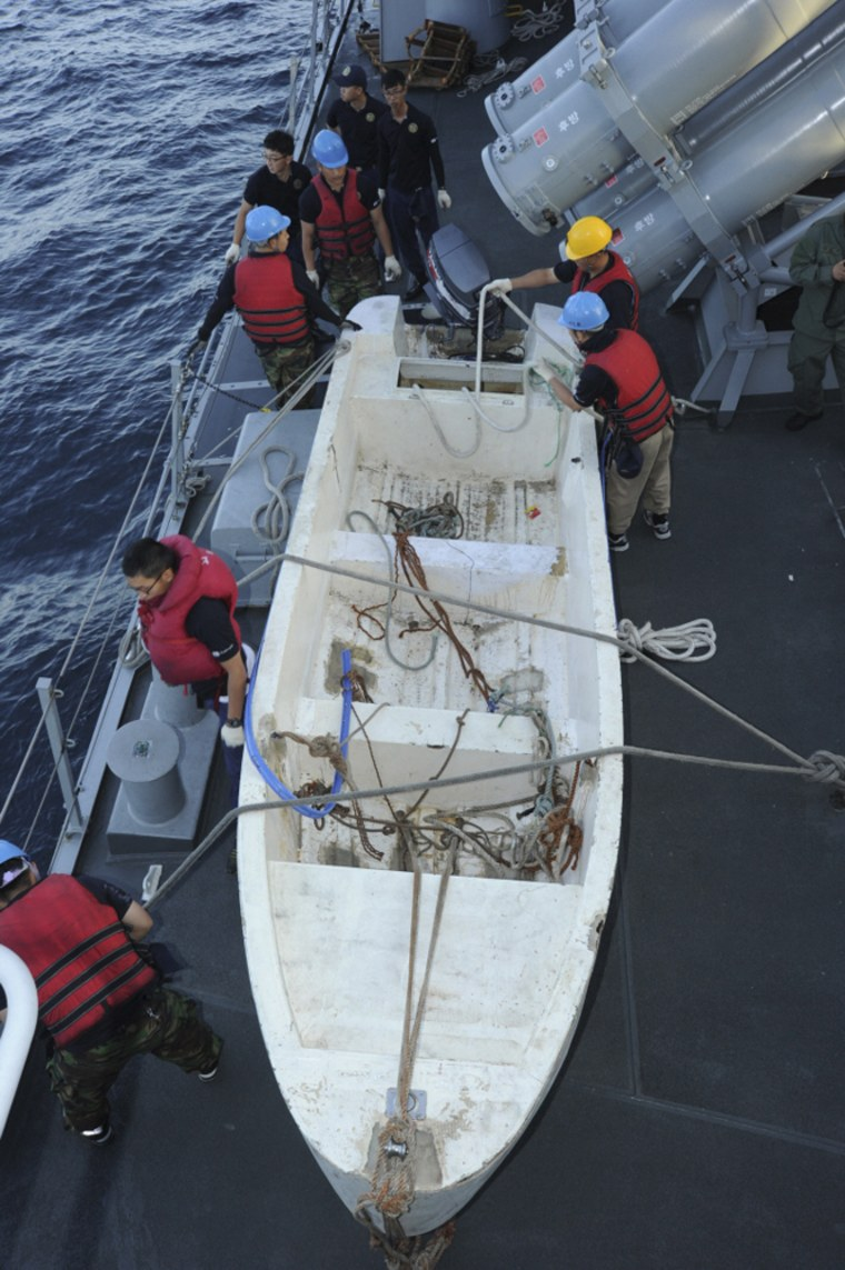 Image: South Korean navy personnel secure a boat used by Somali pirates which was captured in the Arabian Sea