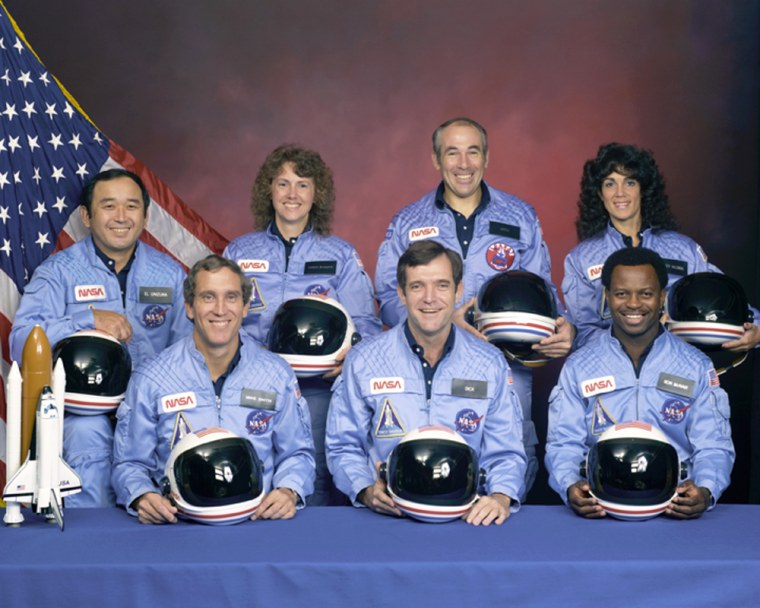 An official portrait shows the STS-51L crew members. Back row, left to right,are mission specialist Ellison S. Onizuka,teacher Christa McAuliffe, payload specialist Greg Jarvis and mission specialist Judy Resnik. In the front row are, left to right,pilot Mike Smith, commander Dick Scobee and mission specialist Ron McNair.
