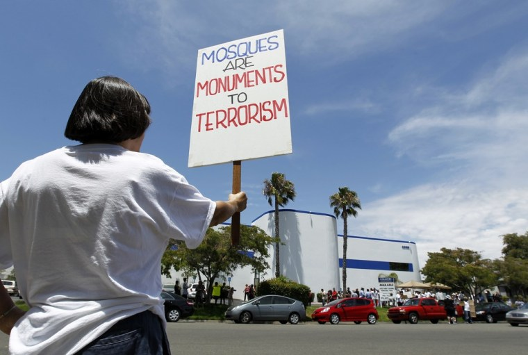 Image: Local citizens protest across the street from a  business warehouse where the Islamic Center of Temecula Valley currently hold their services in Temlecula