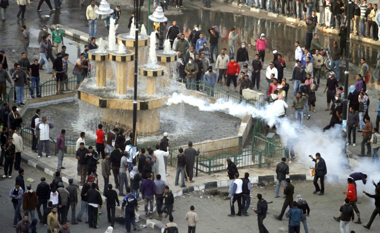 Image: Anti-government demonstrators watch as tear gas is fired by police in an attempt to disperse them  in the port city of Suez