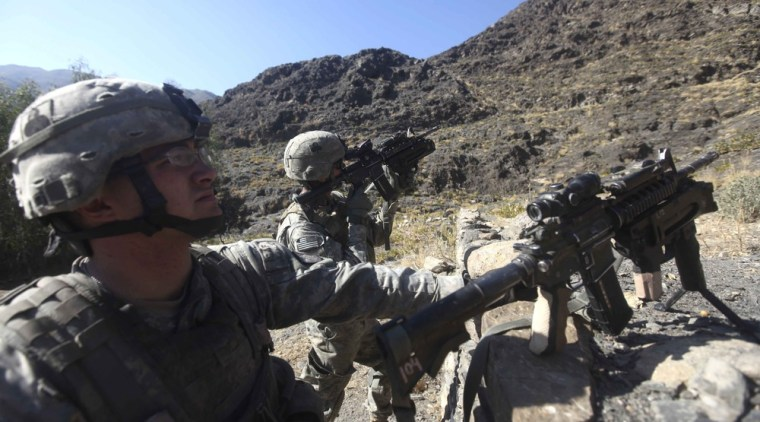 Spc. Andrew Vanderhaeghen, left, from Rochester, Minn., looks on as Spc. Moore Charles, from Angleton, Texas, scan his gun while on patrol in Kunar province in eastern Afghanistan on Sunday, Jan. 2.