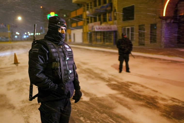 Image: Two members of the Federal Police stand near the border with US during a winter storm at Ciudad Juarez
