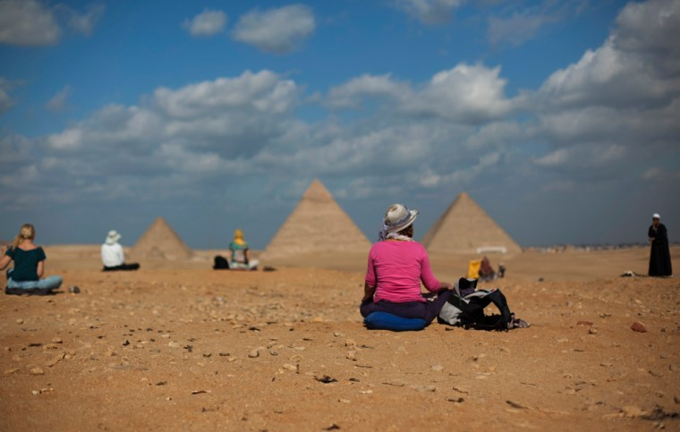 Image: Tourists from Holland sit near the Pyramids