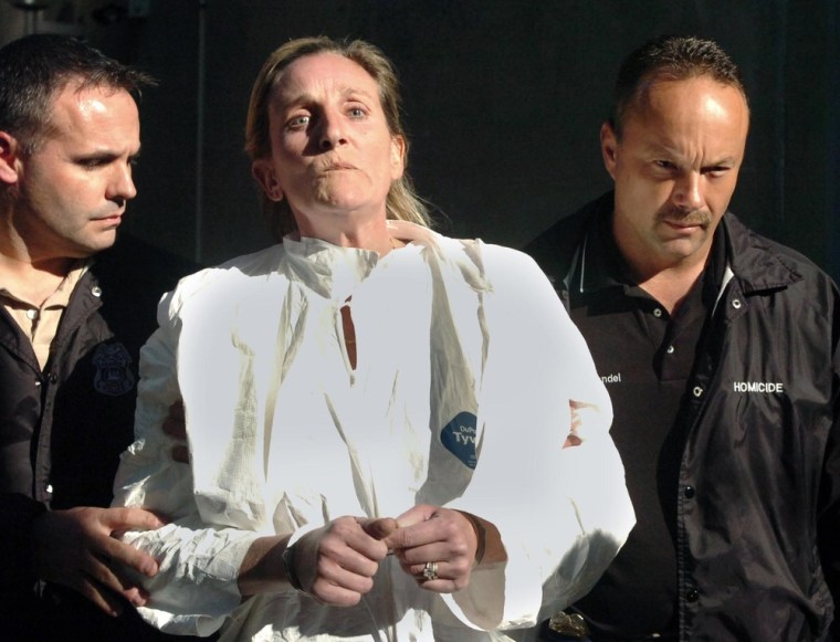 Image: Julie Powers Schenecker is led away from the Tampa Police Department