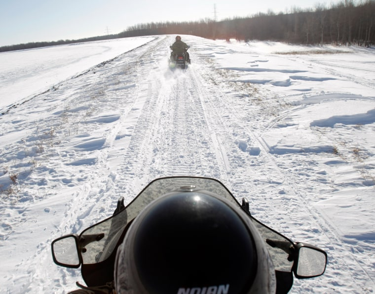 Image: U.S. Border Patrol agents Glen Pickering, front, and Janice Jones ride snowmobiles along the St. Lawrence River